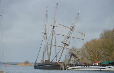 Het schip ligt tegen de vaargeul van het Markermeer nabij de sluis van Muiden. Door wind, weer en water geteisterd zijn de masten de afgelopen week verder uit het lood gezakt. (foto E.J. Bruinekool Fotografie)
