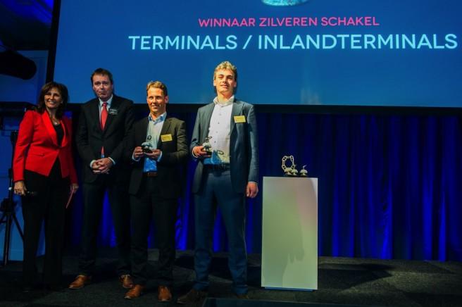 Niels Dekker van RWG (2e van rechts) en Jouke Schaap van APMT (rechts) Maasvlakte 2 met hun prijs. Links presentatrice Astrid Joosten, naast haar